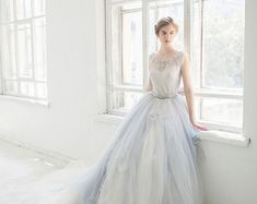 This gorgeous gown features 2 pieces : delightful icy grey tulle wedding skirt Gardenia with ivory tulle underskirt + hand embroidered lace bodysuit.  The top part of this gown is made with unique delicate french lace in icy grey color with silver thread. It is lined with a softest grey silk and has stretchable cotton bottom. The neckline is embroidered by hand with rhinestones, crystals and beads.  The main skirt consists of many layers of the soft tulle in off-white and light grey colors…