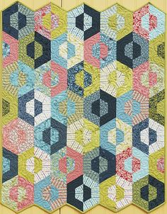 This quilt is beautiful! Props to anyone who can sew hexagons, and put the binding on a quilt shaped like this.