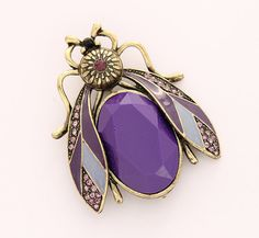 This purple bug brooch measures 2 1/4H x 2W. This piece of costume jewelry in antique gold setting encrusted with amethyst purple crystals and