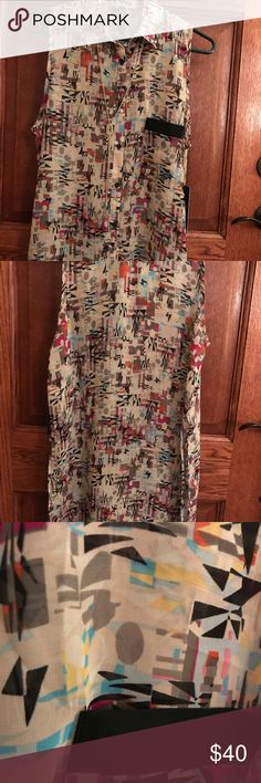 NWT Beige abstract sleeveless button up NWT Beige sheer abstract Sleeveless button up top with black accent on the pocket and side slits. Marcelle Marguax Tops