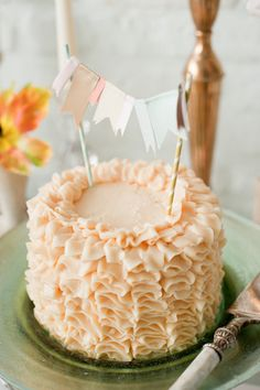 Peach ruffle cake with bunting. Found on Lovey Bride #weddingcake #cakebunting #peach