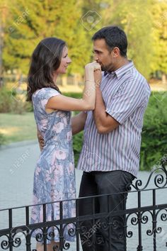 Young Couple In A Park, Man Kissing Woman Hand Stock Photo ...