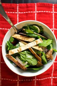 Sliced red onion, mushrooms and sliced crisp flatbreadon a bed of baby spinach.