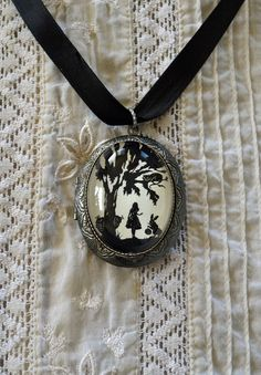 IDEA.  Alice locket... Would be really cool to do some resin pendants with silhouettes like this instead of pictures.