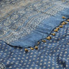 """The """"Blue"""" #handprinted Gaji Silk Sari from Parisera is printed with floral bhuttas all over the body that is set off by a beige border on either side. An attractive geometric motifs in beige and cream colour adorn the blue pallu. The border is repeated on the blue blouse that completes the sari."""