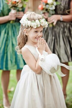 An angelic flower girl dressed in an ivory gown carried a white basket filled with petals and a flower crown composed of green leaves and white blooms. #flowergirl #flowercrown Photography: Jana Williams Photography Read More: http://www.insideweddings.com/weddings/ivory-gold-blush-lakefront-new-hampshire-wedding/412/