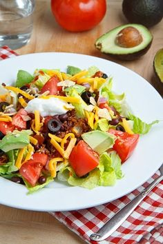 1 tablespoon oil 1 small onion diced 1 clove garlic chopped 1/2 pound ground beef 1 tablespoon taco seasoning 1/4 cup water 4 cups lettuce, sliced 2 large tomatoes, diced 1 cup black beans 1/2 cup salsa 1 avocado, diced 1/4 cup sour cream 2 tablespoons sliced black olives 1/2 cup cheese, shredded 1 handful tortilla chips, crumbled