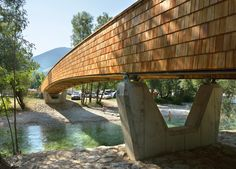 Arching wooden footbridge in Slovenia connects village to mountains.
