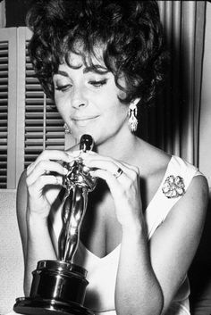 1961: Elizabeth Taylor plays with the Best Actress Oscar she won for the film Butterfield 8