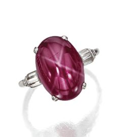 STAR RUBY AND DIAMOND RING, CIRCA 1935.  The oval star ruby cabochon weighing approximately 7.50 carats, flanked by 6 baguette and 8 single-cut diamonds, mounted in platinum