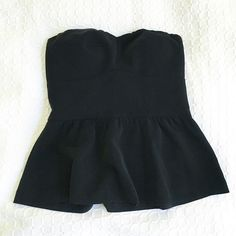 Black Strapless Bustier Structured top. Flattering fit. Classic peplum style top with a sweetheart neckline. Minimalist. Cache Tops