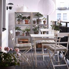 Cienisty balkon, doktórego gorące promienie nie mają dostępu, toidealny azyl naupalne dni. Nie tylko dla nas, aletakże dla tych roślin, które nie lubią nadmiaru słońca. Meble ogrodowe  MÄLARÖ; stół (80x62 cm) iskładane krzesła, regały zestali galwanizowanej HYLLIS, osłonki doniczek MANDEL, posadzka – płytki RUNNEN.