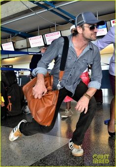Gerard Butler's on the move again - ducking under the ropes at Barbados Airport Sunday September 1, 2013. Looks like a smitten female employee held the rope up for him. Wouldn't you?  :-)