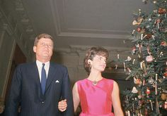 President John F. Kennedy and his wife Jacqueline Kennedy stand by the Christmas tree in the main entrance hall of the White House during a party for their staff ~ Dec. 12, 1962