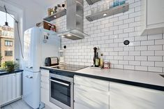 Compact Cooking: A Kitchen in a Closet //  Great small space solution, plus I love the subway tile with dark grout, smeg fridge, the light fixture, and the plant on the radiator!