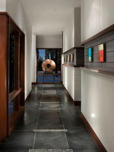 corridor avec carrelage de sol en gris foncé et niches de rangement habillées de bois