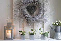 White winter mantel display with twig wreath and white roses in galvanized containers.