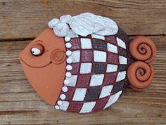 Ryba se závojem Tento výrobek velmi pěkně vypadá ve dvojici s Rybou s kloboukem. Ručně vyráběná závěsná dekorace, co kus to jedinečný originál. Barevné provedení červenice Rozměr 20x17cm K zavěšení na zeď je v kachli zapracován nerezový drát
