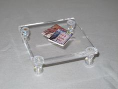 use a clear acrylic stamping block with either 2 stacked pony beads for legs or clear pushpins