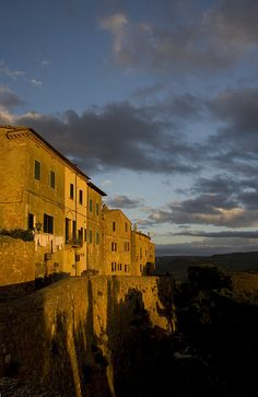 Houses atop the city wall of Pienza at sunset.
