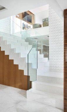 Nesta cobertura em Ipanema, a escada faz o papel de uma escultura. Segundo o arquiteto Rodrigo Barbosa, seu guarda-corpo é feito de cristal transparente para que a pessoa possa observar o painel de mosaicos branco que orna a parede de subida