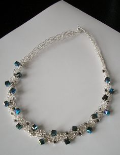 Crocheted sterling silver coated wire necklace with swarovski crystal cubes.