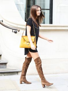 Emily Ratajkowski is wearing a black t-shirt dress with thigh high brown suede boots, a yellow shoulder bag and glasses.