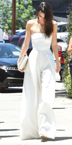 Kendall Jenner in a Solace London white strapless wide-leg jumpsuit, a white clutch and nude pointed toe heels