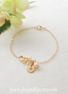 Shiny golden leaf foliage bracelet adorn with pretty freshwater pearl will become a charming addition to your jewelry collection. Personalized with a hand stamped disc charm with the letter of your choice. www.foxandfigs.etsy.com - $25