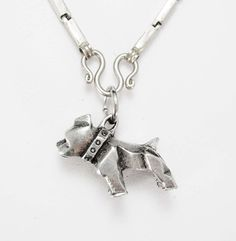 This mack truck bulldog has the word mack on his collar and he is so chiseled and strong looking. He hangs from a thick sterling chain that has