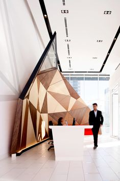 Minto | Faceted Canopy Wall // A faceted millwork canopy wall frames the reception desk in the lobby of the latest Minto Condo development // Commercial Architecture Wood Fabrication Interior Design