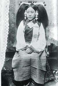 """Portrait of an aristocratic woman of Lhasa wearing typical Central Tibetan coral and pearl headdress, turquoise ear-rings, a """"gau"""" (amulet box) at her neck, and the married woman's striped apron. The pose and setting, with the European furniture and textiles of a wealthy Lhasa family, is carefully arranged in the style of Indian studio photography."""