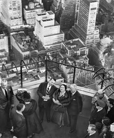 """Oct. 29, 1954: A visit by Queen Elizabeth the Queen Mother to New York included being whisked to the 102nd floor observation deck of the Empire State Building. She charmed her American guides, chatting with them amiably and was """"nearly mobbed"""" as she left the building."""