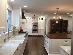 Historic kitchen with Carrara marble perimeter countertops and a butcher block island.  White subway tile backsplash and dark hardwood floors.  White kitchen by Stoneshop from Cherry Hill, NJ.