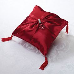 Measuring 8 inches wide, this elegant Red Satin Ring Bearer Pillow is covered in red satin. The front is decorated with red satin ribbon tied together with a crystal band ornament.