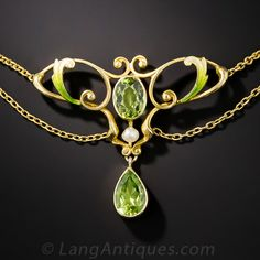 Art Nouveau Peridot and Enamel Necklace. They don't come any sweeter or lovelier than this original Art Nouveau jewel, circa 1900, glistening with a luscious pair of lime green peridots embellished with sinuous golden scrolls and a dash of matching shaded enamel. Delicate swags are supported by a pair lustrous freshwater pearls.