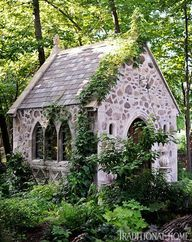 A stone chapel with stained-glass windows is nestled into the trees at the edge of this unique property. - Traditional Home ® / Photo: Matthew Benson