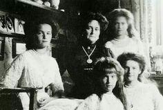 Empress Alexandra sitting with Grand Duchesses Olga, Anastasia, Tatiana, and Maria Romanov.