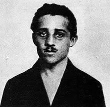"""Gavrilo Princip (1894-1918) is een Bosnische Serviër, die zich aansluit bij de geheime nationalistische beweging """"De Zwarte Hand"""". Na een mislukte aanslag op Franz Ferdinand van partijgenoten komt hij hem later op de dag bij toeval tegen en schiet hem en zijn vrouw neer. Hij krijgt hiervoor twintig jaar cel, maar overlijdt in 1918 aan tuberculose. Zijn daad bracht Oostenrijk ertoe Servië de oorlog te verklaren."""