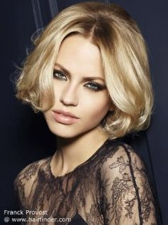 Short blonde bob with a center part. Wavy styling for volume.