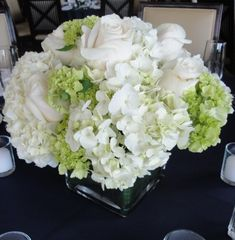 White hydrangea centerpieces with accents of mini green hydrangea/viburnum and roses