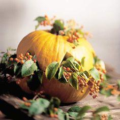 une citrouille décorative et remplie de feuilles vertes et baies