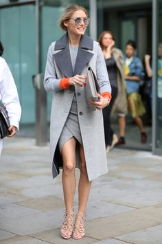 Olivia Palermo wearing a two-toned sleeveless coat, grey crew neck sweater, grey asymmetric skirt, and strappy nude heels