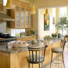 A variety of neutral and pale wood tones can create a light and airy kitchen look. Be sure to anchor with a few deeper tones like the wrought iron chairs and black accents on the stove.
