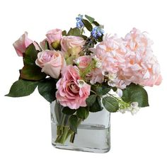 Bring the beauty of nature into your home with this lovely faux floral arrangement, showcasing lush camellia and hyacinth nestled in a glass vase.
