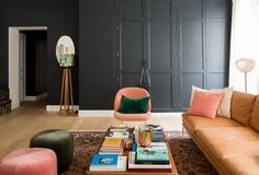 super dark charcoal gray wall with built-ins + pink, peach + green upholstered furniture