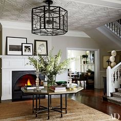 A custom-made Jasper light fixture hangs in the entrance hall of Net-a-Porter executive chairman Natalie Massenet's London home, which was decorated by Michael S. Smith; the vintage Karl Springer table is from Liz O'Brien, and the carpet is by Kravet.