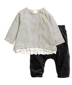 Schwarz. CONSCIOUS. Set aus weicher Bio-Baumwolle mit Shirt und Hose. Jerseyshirt mit Knöpfen an der einen Schulter, Spitzenborte am Saum und etwas