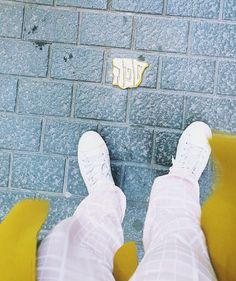 Mallorca im Februar. Rosa Hose, grüner Wollmantel und weiße Schuhe.