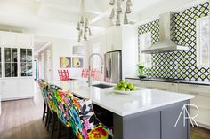 Gorgeous colorful kitchen with patterned backsplash, flower pattern stools, and bright art